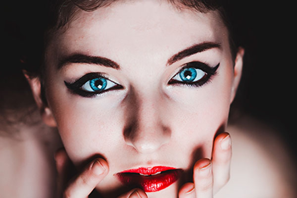 image of a woman with red lipstick and permanent eye makeup